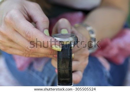 Female hands with manicure adjusting or winding wrist watch, concept of time, closeup with selective focus - stock photo