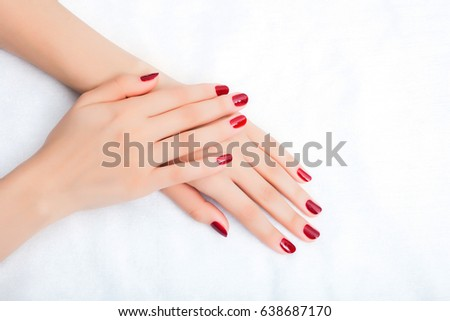 Female hands with manicure and red lacquer on a white table