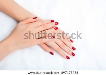 Female hands with manicure and red lacquer on a white table in the beauty salon