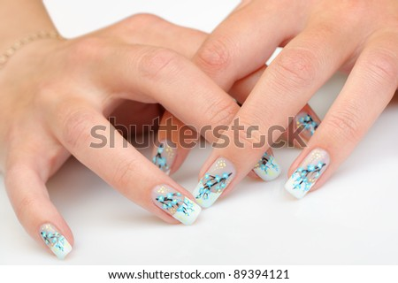 Female hands with manicure close up. Drawing of a branch with blue flowers. It is isolated on a white background.
