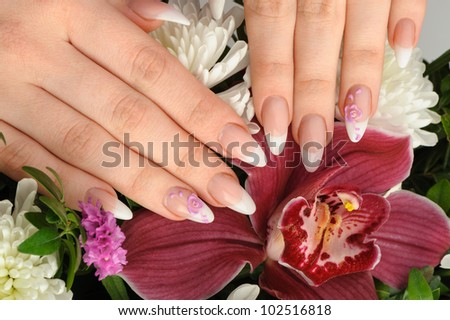 Female hands with manicure closeup. Against an orchid
