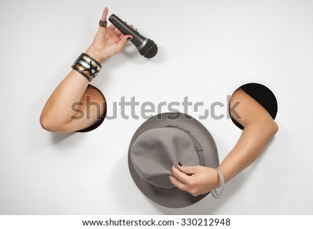 Female hands with microphone and hat - stock photo