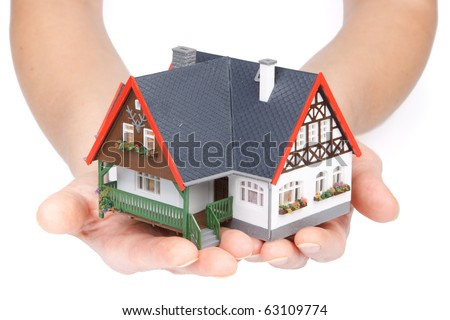 Female hands with model of house on a white background. Concept  of buying and insuring  real estate. - stock photo