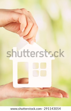 Female hands with model of house on blurred background
