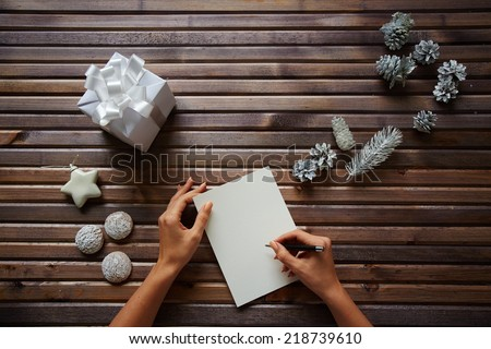 Female hands with pen over piece of paper with spice-cakes, decorative silver cones, giftbox and white toy star near by - stock photo