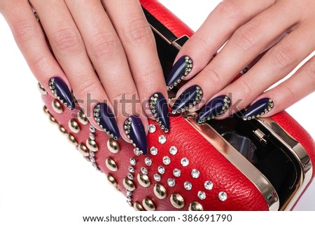 Female hands with purple manicure with rhinestones holding a red handbag - stock photo