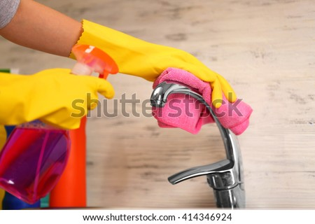 Female hands with rag and detergent spray cleaning a tap in the kitchen - stock photo