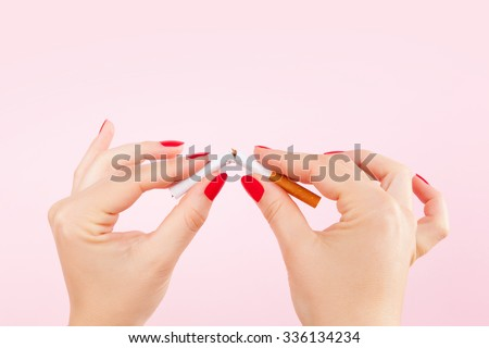 Female hands with red fingernails braking the last cigarette isolated on pink background. Quit smoking new year resolution. - stock photo