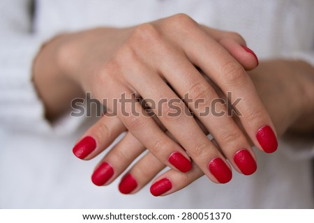 Female hands with red nails on a white background. On her nails red manicure. - stock photo