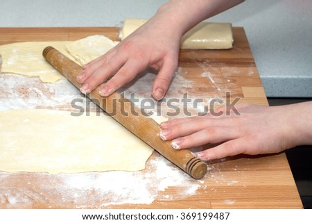 Female hands with rolling pin preparing dough for baking on brown wooden cutting board on kitchen table. Closeup view