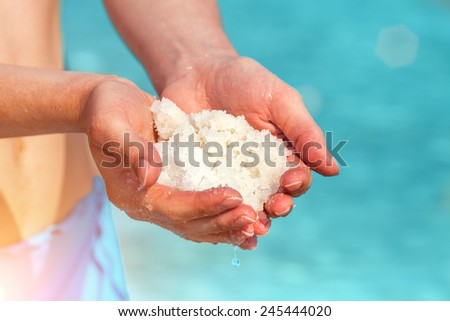 Female hands with sea salt for spa from Dead Sea - stock photo