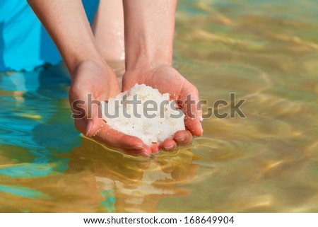 Female hands with sea salt from Dead Sea - stock photo