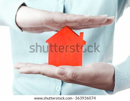 Female hands with small model of house