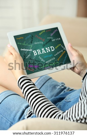 Female hands with tablet on home interior background