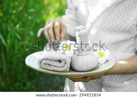 Female hands with tray of spa products over green reeds on river