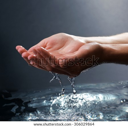 Female hands with water splashing on dark background