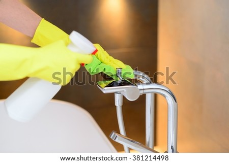 Female hands with yellow rubber protective gloves cleaning bath mixer with green cloth and spray detergent. Spring cleaning - stock photo