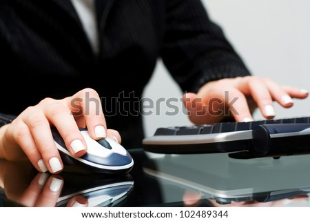 Female hands working on computer - stock photo