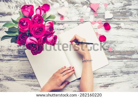 Female hands writing in open notebook and bouquet of roses on old wooden table. Top view. Toned image - stock photo
