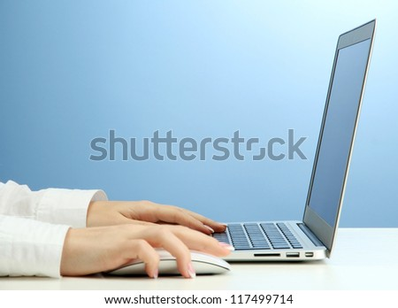 female hands writing on laptot, on blue background - stock photo