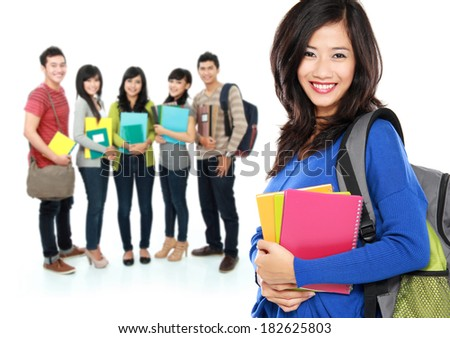 Female happy student carrying bag and books with a group of people at the background