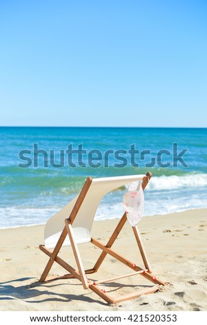 Female hat and deckchair on the beach vacation, sunny outdoors background