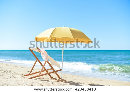 Female hat, chair and umbrella on stunning tropical beach vacation background - stock photo