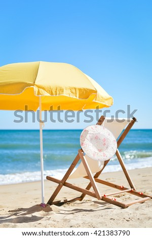 Female hat, chair and umbrella on stunning tropical beach vacation background. Happy holiday location - stock photo