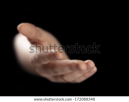 female helping hand from darkness, selective focus - stock photo