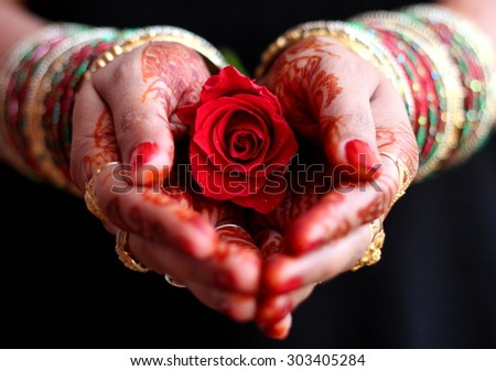 Female henna hands with red rose greeting people  - stock photo