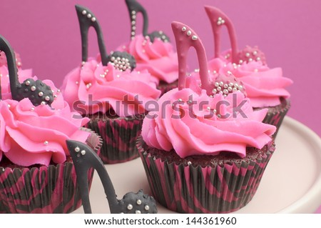 Female high heel shoes decorated pink and black red velvet cupcakes with high heel shoes for teenage, female birthday, or wedding bridal shower - close up. - stock photo