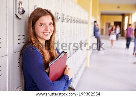 Female High School Student Standing By Lockers - stock photo