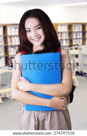 Female high school student with long hair, standing in the library while smiling at the camera