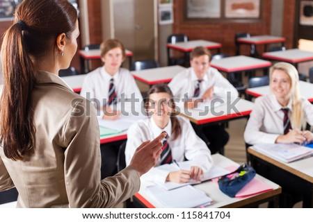 female high school teacher teaching in classroom - stock photo