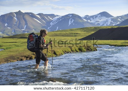 Female hiker crossing a river on the famous Laugavegur trail on Iceland.