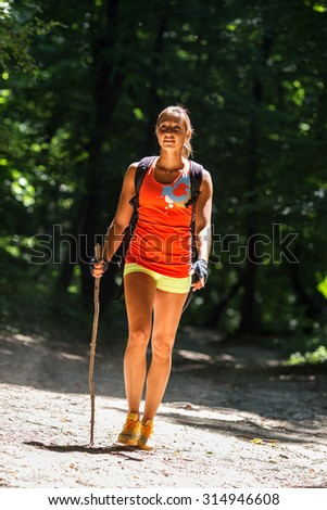 Female hiker hiking trough forest.