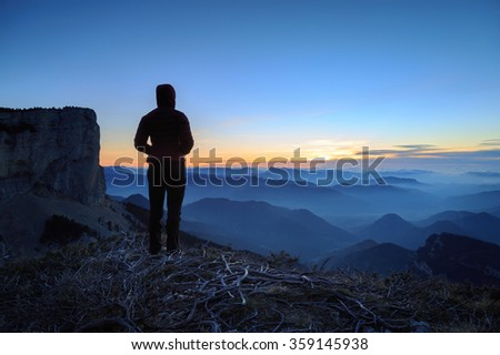 Female hiker looking at the tranquil sunset over the hills and mountains in France.