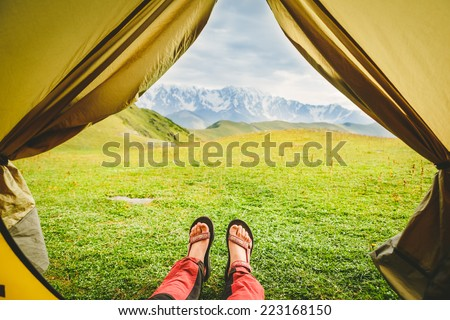 Female hiker lying in tent with a view of mountain - stock photo
