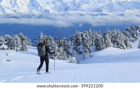 Female hiker on snowshoes in the snow covered French mountains during a micro adventure. Shallow focus. - stock photo