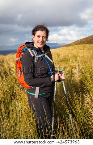 Female hiker posing in the grass at the foot of Carrauntoohil in County Kerry in Ireland
