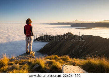 Female hiker reaching her goal at the mountain top and looking at majestic panoramic view of the italian western Alps with M. Viso peak in the background. Wide angle view at sunset. - stock photo