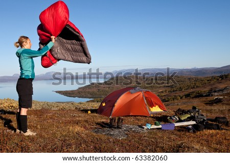 female hiker shakes the sleeping bag in front of a tent in lapland - stock photo