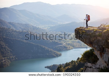 Female hiker standing on cliff and enjoying valley view - stock photo