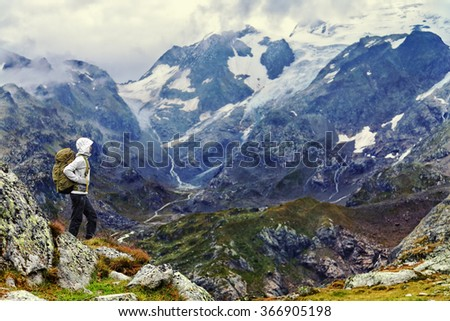 Female hiker standing on mountain on hiking trek. Side view of woman in warm clothing carrying backpack. Woman is enjoying idyllic view of mountain range. - stock photo