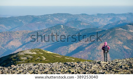 Female hiker standing on mountain plato enjoying beautiful overlook on the mountains with backpack on. Rear view. Ecotourism and healthy lifestyle concept. Copy space. - stock photo