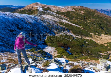 Female Hiker standing on snowy Rocks admiring scenic Winter Mountain View carrying Backpack and walking Pole - stock photo