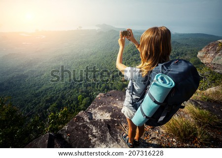 Female hiker taking picture of the valley from top of the hill - stock photo