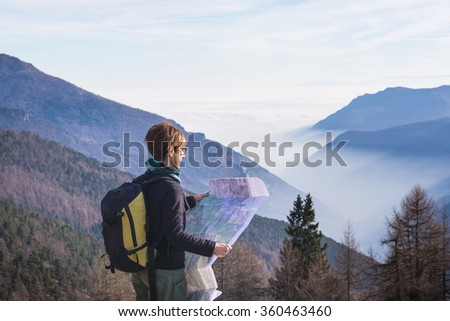 Female hiker with backpack reading trekking map while resting at panoramic point on the italian Alps. Mist and fog in the valley below, larch and pine tree forest around. Selective focus. - stock photo