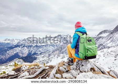 Female hiker with backpack sitting on rock of mountain top enjoying view of valley below - stock photo