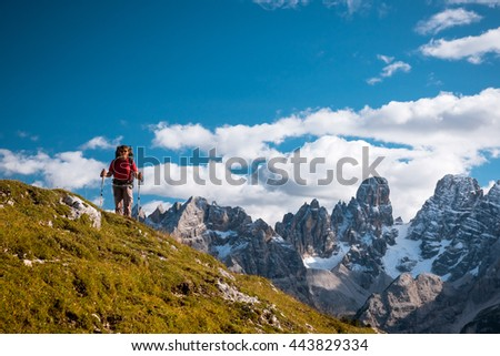 Female hiker with backpack standing on path in Dolomite mountains - stock photo